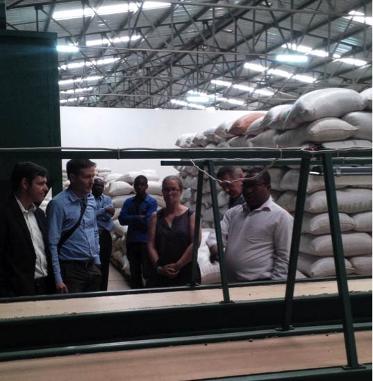 NASFAM Commercial Manager Alexander Chikapula (far right) shows the USAID delegation around the NASFAM warehouse in Lilongwe